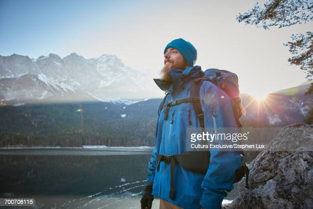 Young male hiker looking out to Lake Eibsee in winter, Zugspitze, Bavaria, Germany