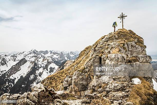 Young male hiker on peak of Klammspitze mountain, Oberammergau, Bavaria, Germany