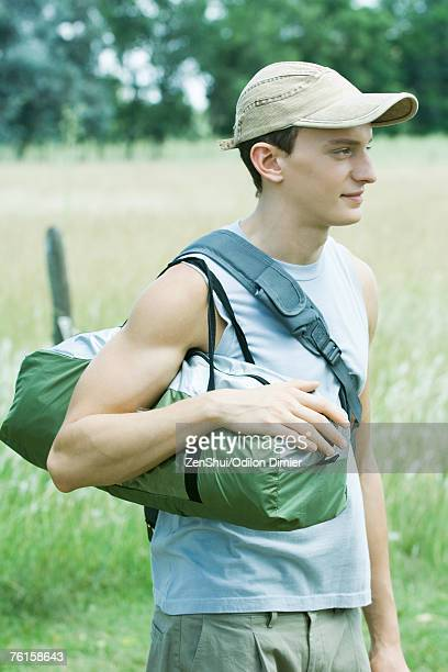 Young male hiker standing in field