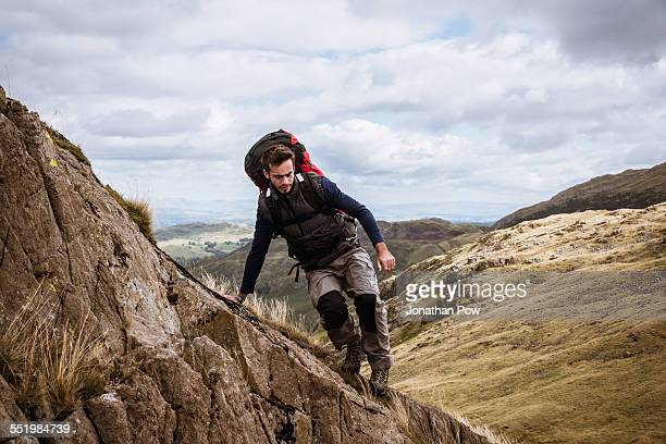 Young male hiker stepping from rock, The Lake District, Cumbria, UK