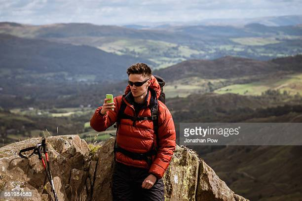 Young male hiker taking smartphone selfie from mountain, The Lake District, Cumbria, UK