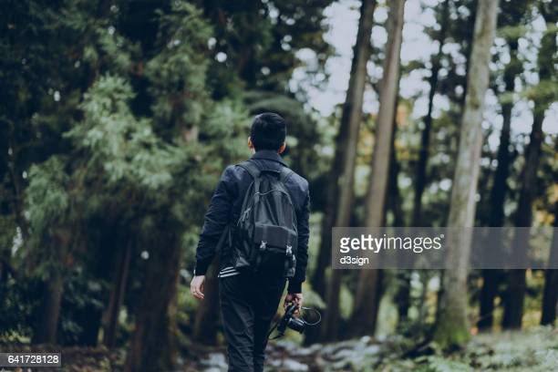 Young male hiker walking in forest and taking photos of the wild