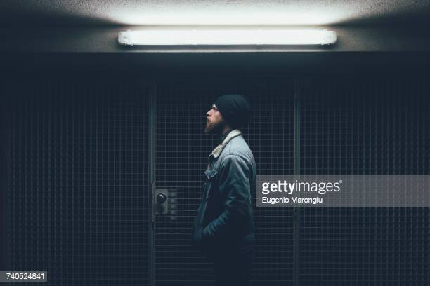 Young male hipster in dark city doorway at night