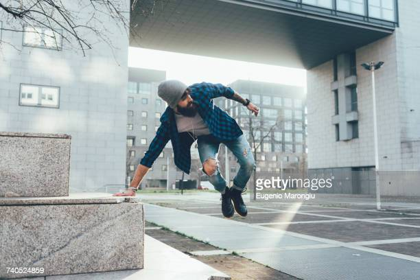young male hipster jumping mid air practicing parkour in city - le parkour stock-fotos und bilder