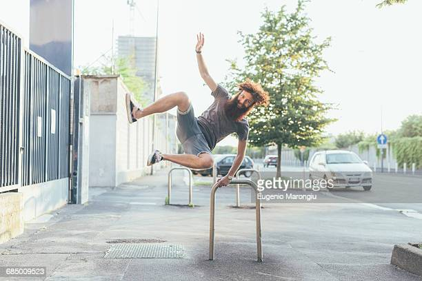 Young male hipster kicking up heels on sidewalk