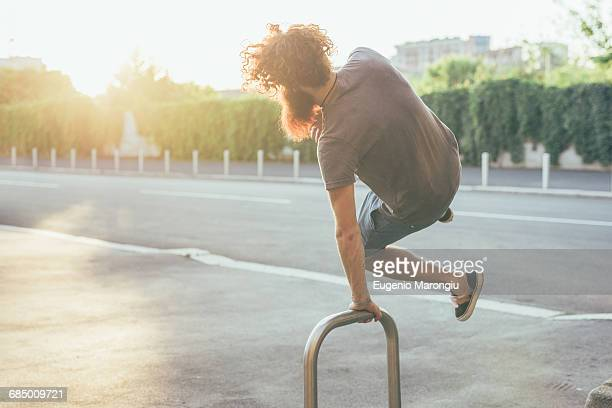 Young male hipster kicking up heels on sunlit sidewalk