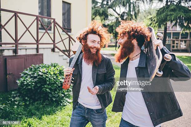 Young male hipster skateboarder twins with red beards strolling in park