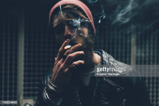 young male hipster smoking cigarette in dark city doorway at night - machismo fotografías e imágenes de stock