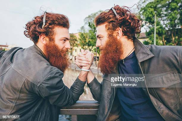 Young male hipster twins with red hair and beards arm wrestling on bridge