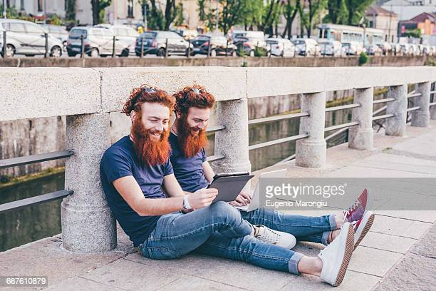 Young male hipster twins with red hair and beards browsing digital tablet on bridge