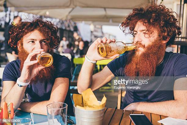 Young male hipster twins with red hair and beards drinking beer at sidewalk bar
