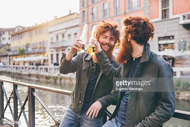 Young male hipster twins with red hair and beards making a toast on canal waterfront