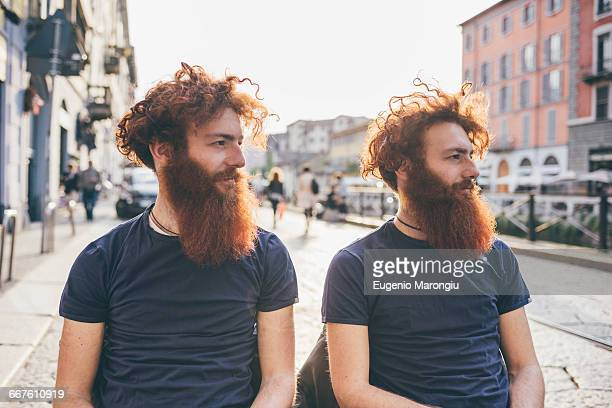 young male hipster twins with red hair and beards on city street - identical twin stock pictures, royalty-free photos & images