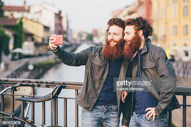 Young male hipster twins with red hair and beards taking smartphone selfie on canal waterfront