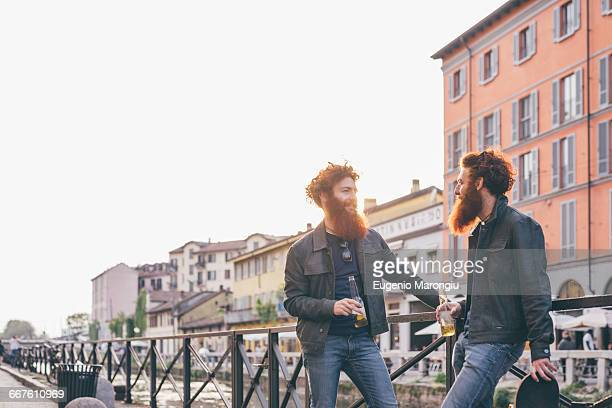 Young male hipster twins with red hair and beards talking on canal waterfront