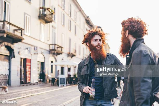 young male hipster twins with red hair and beards talking on city street - identical twin stock pictures, royalty-free photos & images