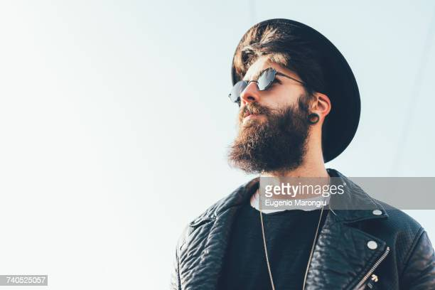 Young male hipster wearing sunglasses and trilby looking up