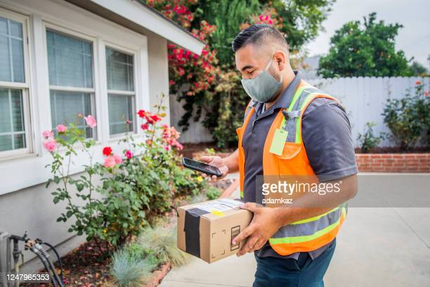 young male hispanic delivery man takes package to home wearing a face mask - adamkaz stock pictures, royalty-free photos & images