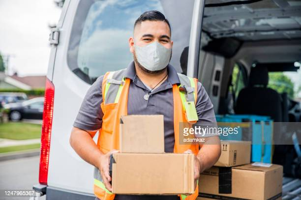 young male hispanic delivery man takes package to home wearing a face mask - delivery person stock pictures, royalty-free photos & images