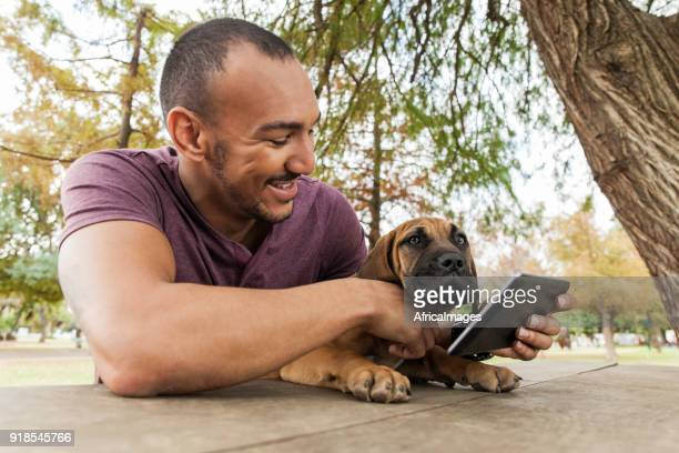 Young male holding a digital tablet with his puppy on his lap.
