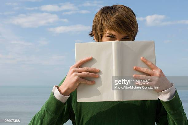 Young male holding book in front of face, portrait