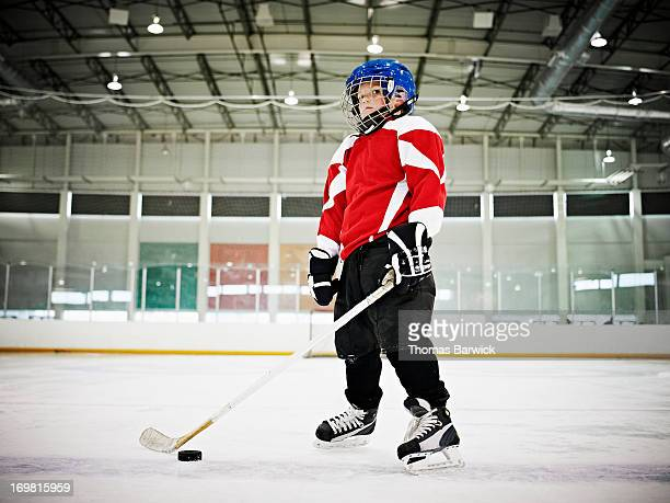 young male ice hockey player standing on ice - hockey stock pictures, royalty-free photos & images