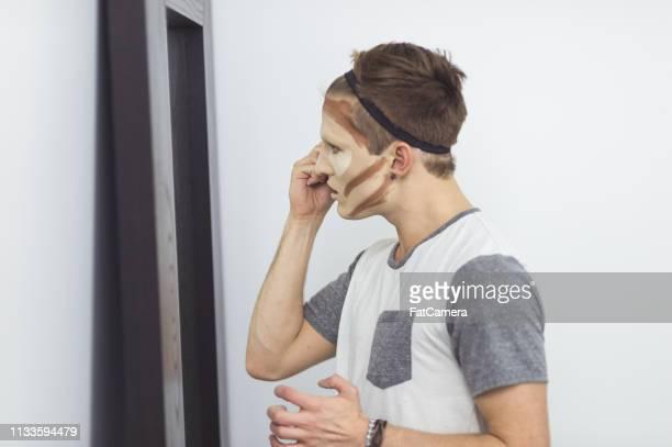 junge mann in einer umkleidekabine auf make-up - crossdresser stock-fotos und bilder