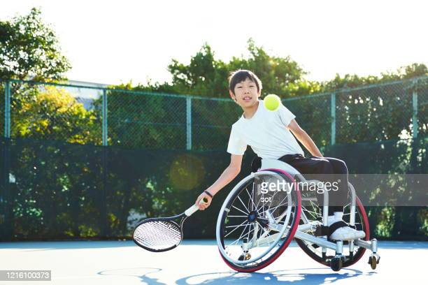 young male in a wheelchair playing tennis on a tennis court - 車いすテニス ストックフォトと画像