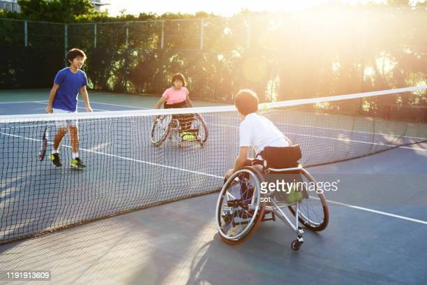 a young male in a wheelchair playing tennis with a young female in a wheelchair and a young male - 車いすテニス ストックフォトと画像
