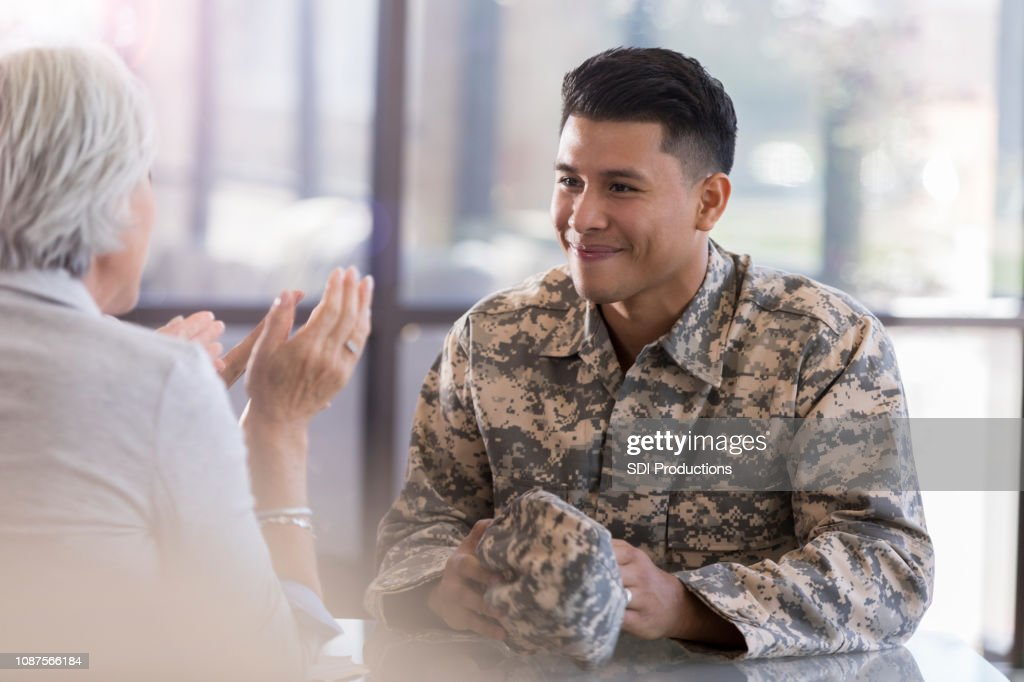 Young male in uniform smiles at counselor : Stock Photo