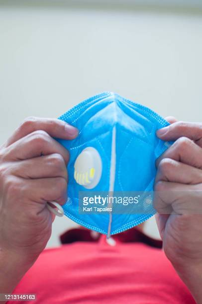 a young male is about to wear a face mask indoor - shielding stock pictures, royalty-free photos & images