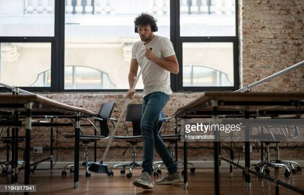 young male janitor cleaning an office while listening to music with wireless headphones - broom sweeping stock pictures, royalty-free photos & images