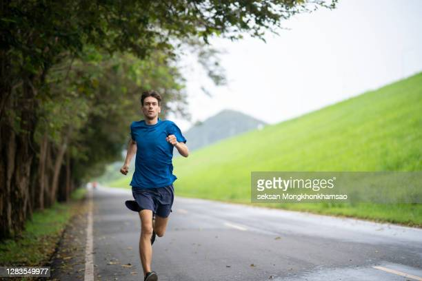 young male jogging in the park - schlank stock-fotos und bilder