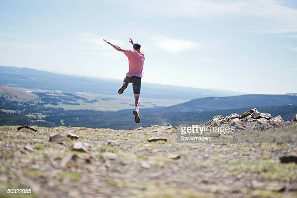 Young male jumping off mountain top