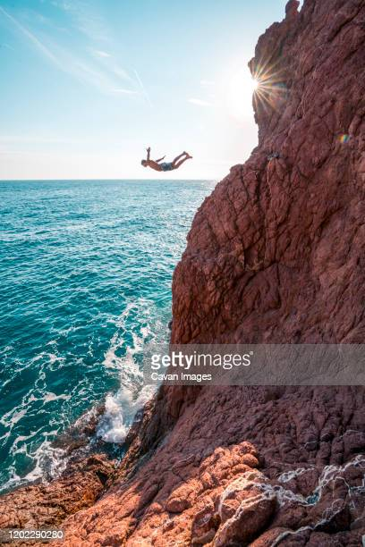 young male jumps from red sand stone cliff into blue ocean - var stock pictures, royalty-free photos & images