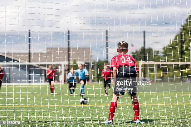 young male keeper waiting for an opponentts attempt a goal - fat goalkeeper stock pictures, royalty-free photos & images