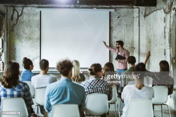 junge männliche leiterin, die eine präsentation vor einer großen gruppe von menschen in boardroom. - seminar stock-fotos und bilder