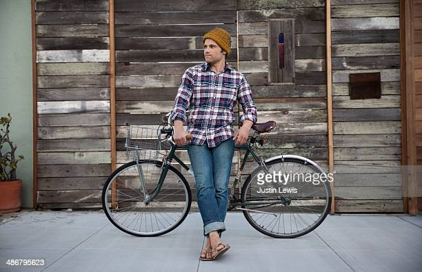 Young male leans against bicycle w/wooden house