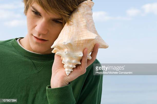 young male listening to conch shell - conch shell stock pictures, royalty-free photos & images