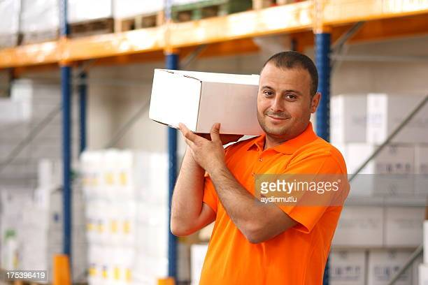 Young male manual worker holding a white box on his shoulder