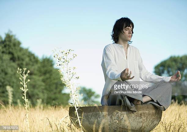 Young male meditator in lotus position in field