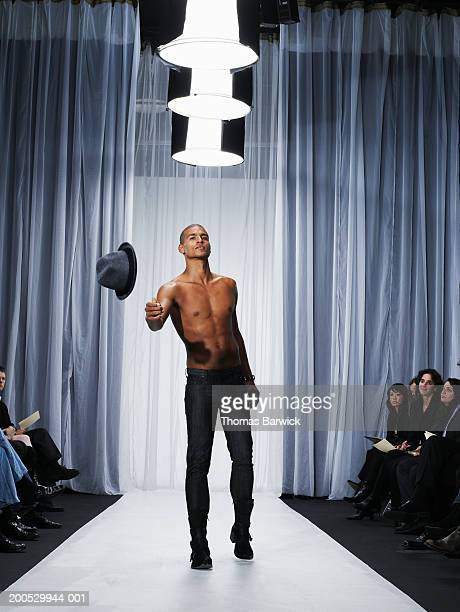 young male model throwing hat from catwalk - indian male model stock-fotos und bilder
