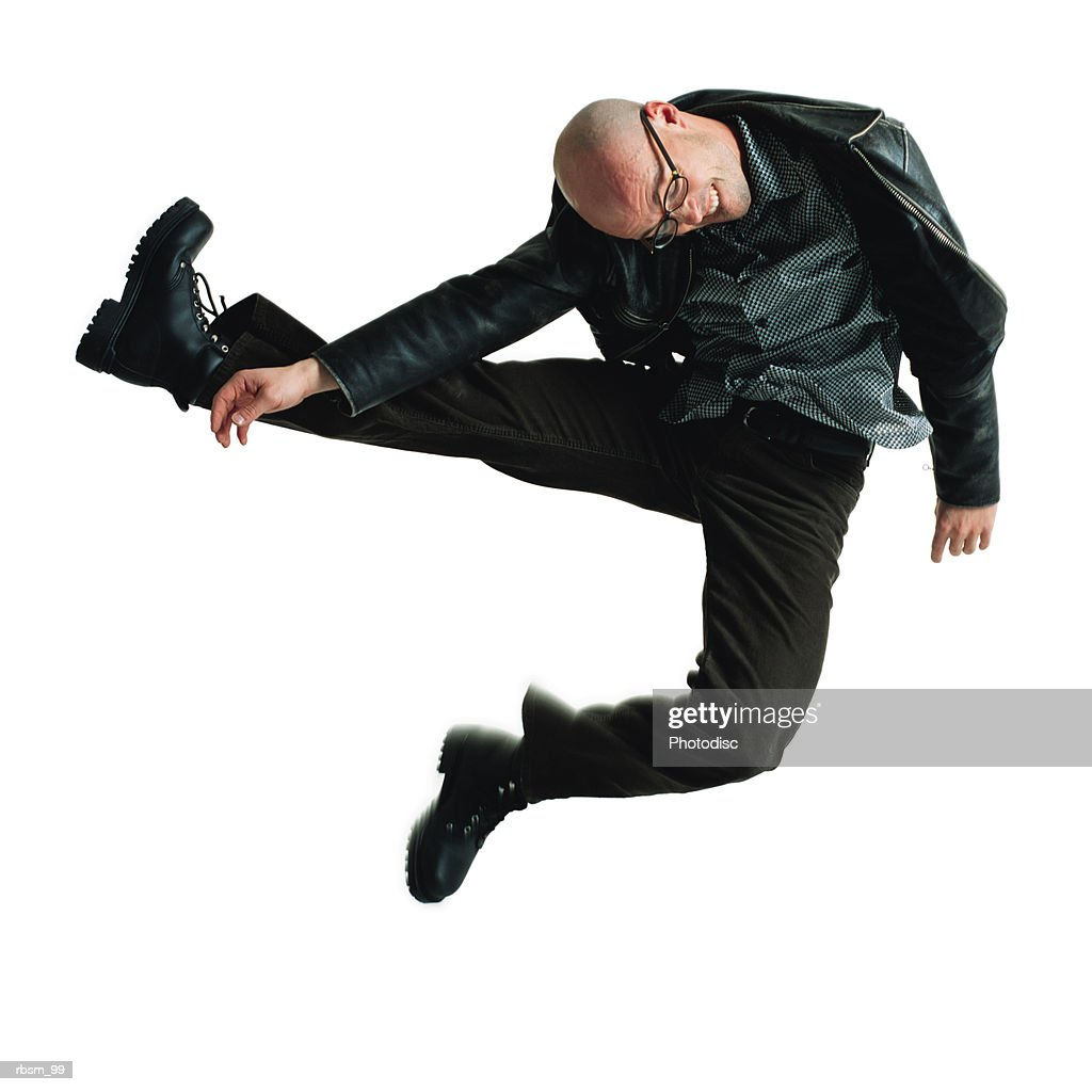 young male modern dancer dressed in black and wearing glasses throws his body sideways into the air : Foto de stock