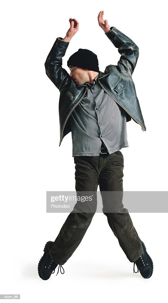 young male modern dancer in black leather jacket knit cap balances on toes raises his arms overhead : Stockfoto