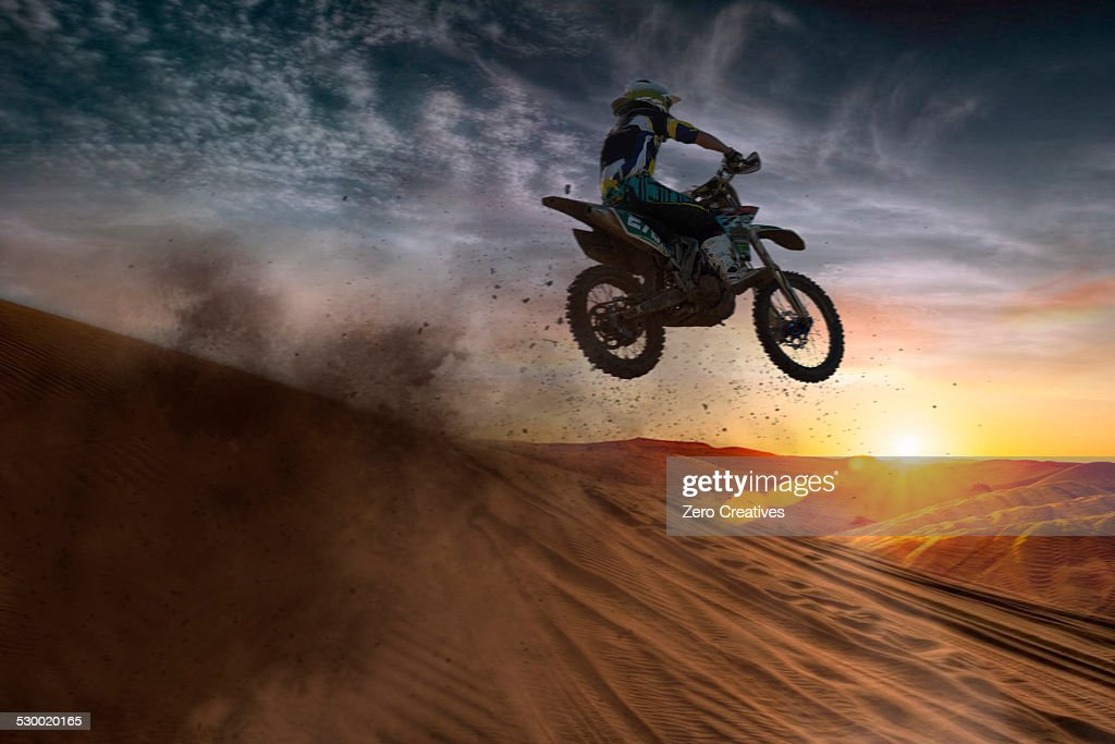 Young male motocross racer jumping mid air at sunset : Stock Photo