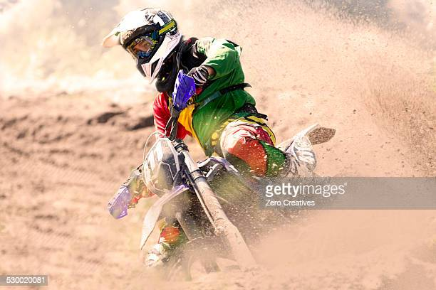 Young male motocross rider racing and leaning into mud track