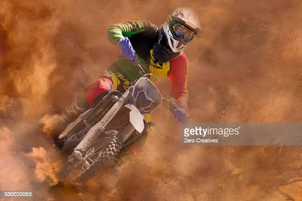 Young male motocross rider racing in dust
