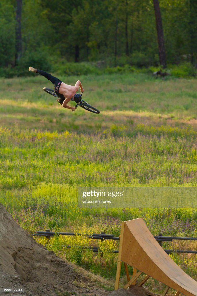 A young male mountain bike rider does a 360 nac-nac while riding off a wooden ramp jump. : Stock Photo