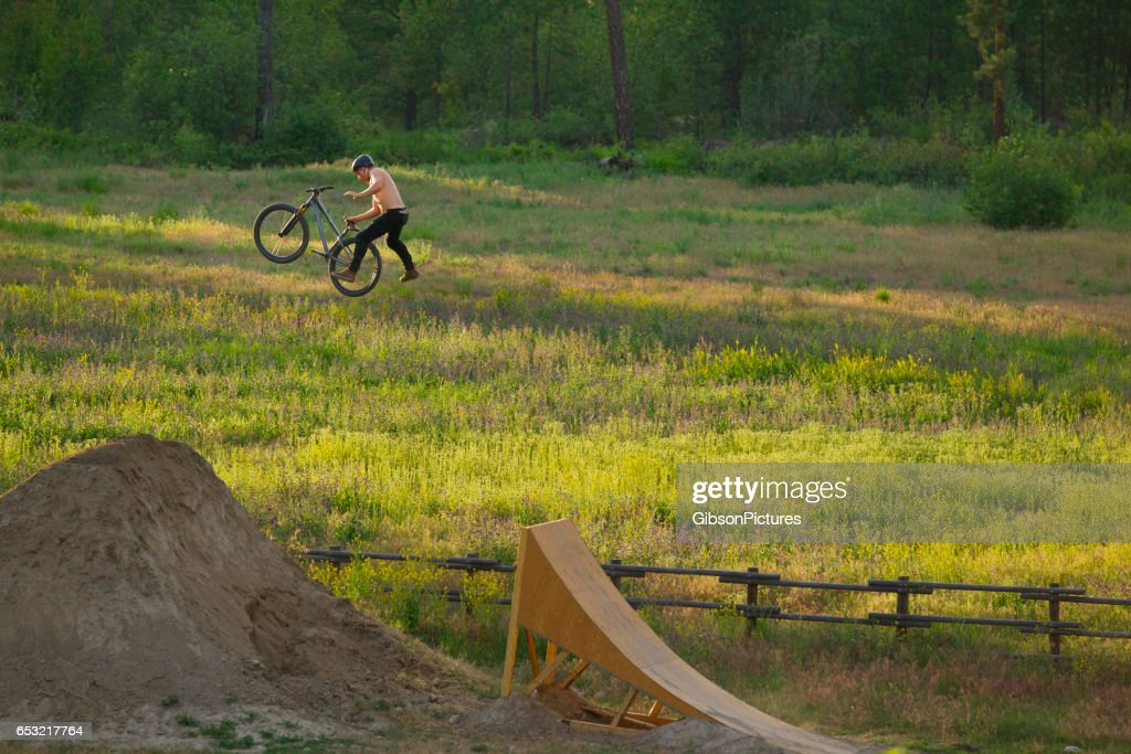 A young male mountain bike rider does a one-handed cannonball trick while riding a wooden ramp jump on a sunny day.. : Foto stock