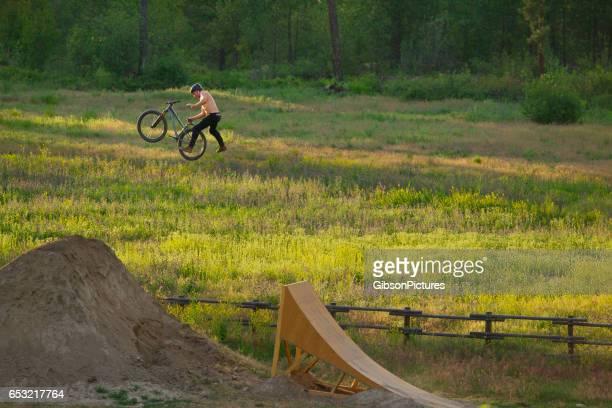 Un cycliste de montagne mâle jeune fait un tour de boulet de Canon avec une seule main pendant que vous roulez une rampe en bois sauter sur une journée ensoleillée...